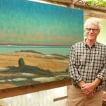 "Painter Allen Whiting in his studio with his work, ""Vineyard Sound From Menemsha."" Photo: Martha's Vineyard Times"